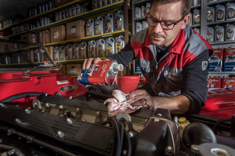 Un mecánico reponiendo aceite en el motor de un vehículo